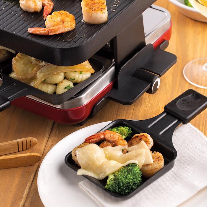 ein raclette grill mit gardinen und raclette käse kleines schwarzes pfännchen mit brokkoli gardinen und geschmolzenem käse