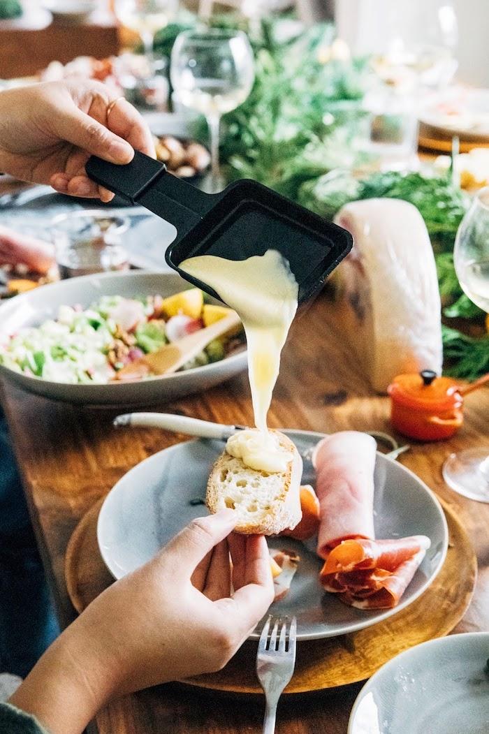 ein schwarzes pfännchen mit geschmolzenem käse für raclette raclette zutaten brot und käse teller mit schinken