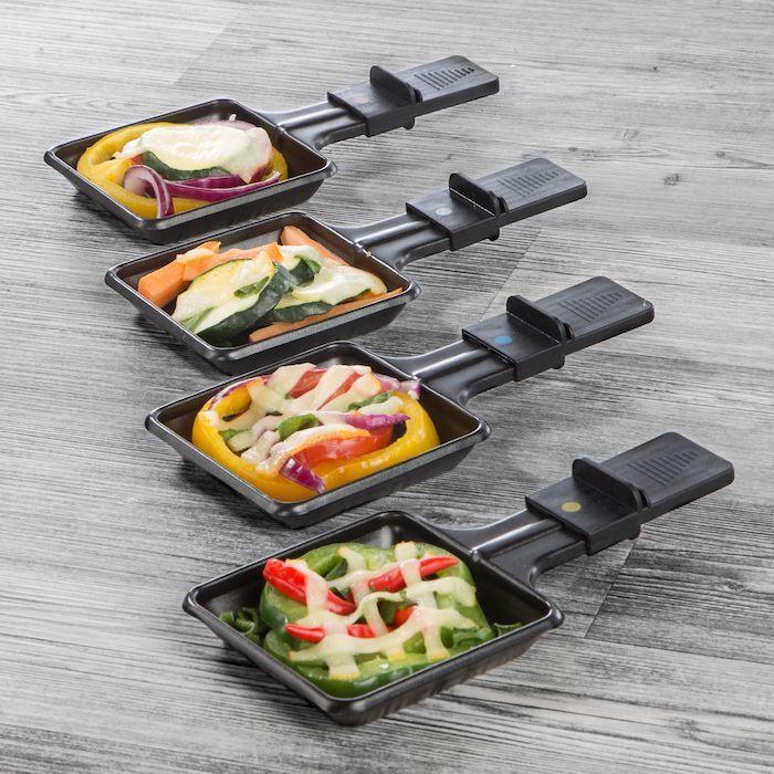 ein tisch aus holz raclette zutaten vier schwarze kleine pfännchen mit gemüse und käse grüne und gelbe paprika
