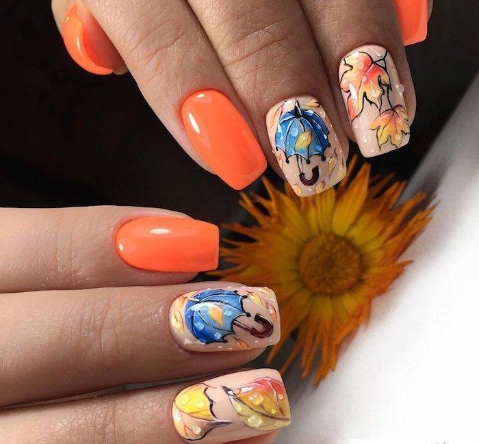 eine große orange blume zwei hände einer frau fingernagellack orange kleine blaue regenschirme und orange blätter