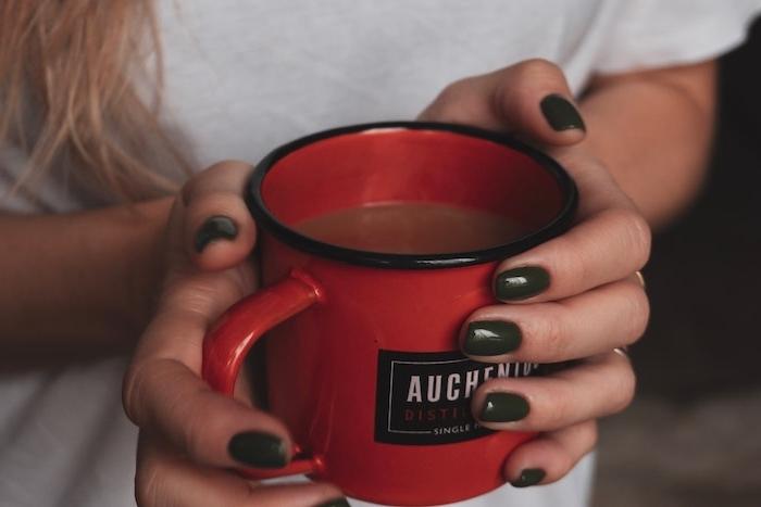 eine große rote tasse mit kaffe eine hand mit einem dunklen nagellack und mit einem weißen t shirt