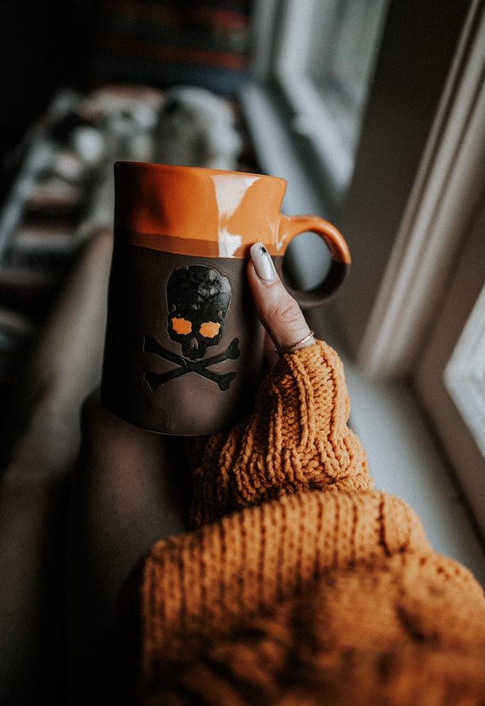 eine halloween tasse mit einem großen schwarzen totenkopf fenster eine frau mit hand mit einem orangen nagellack