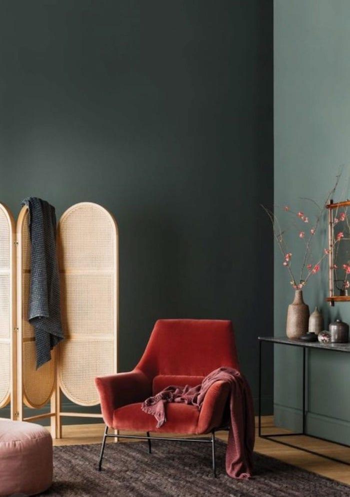 eleganter roter sessel wandfarbe grün skandinavische deko wohnzimmer spanische wand holz dunkler teppich pinker ottoman