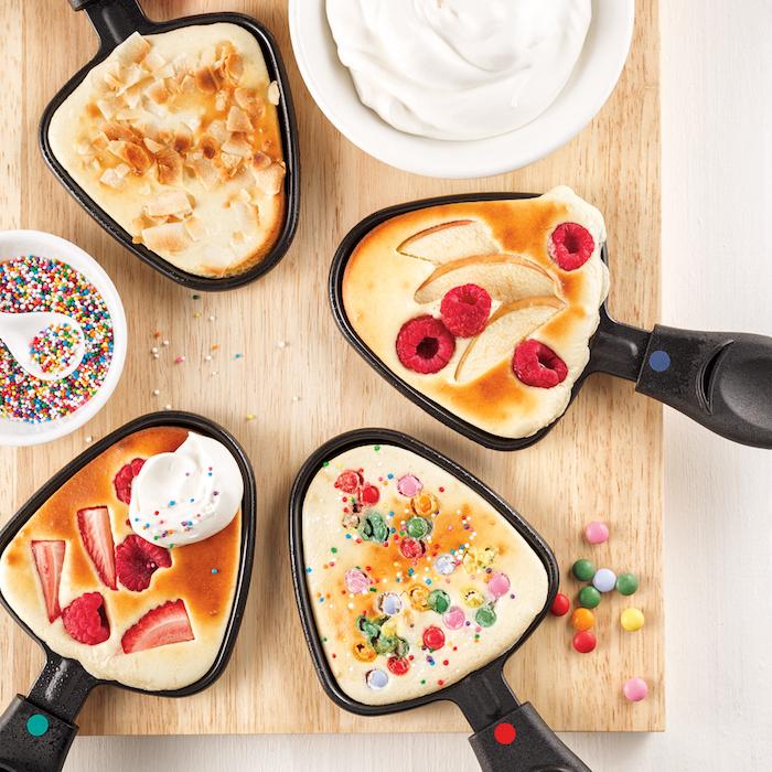 erdbeeren kuchen für raclette ein holzbrett und vier kleine schwarze pfännchen für raclette raclette rezepte ideen
