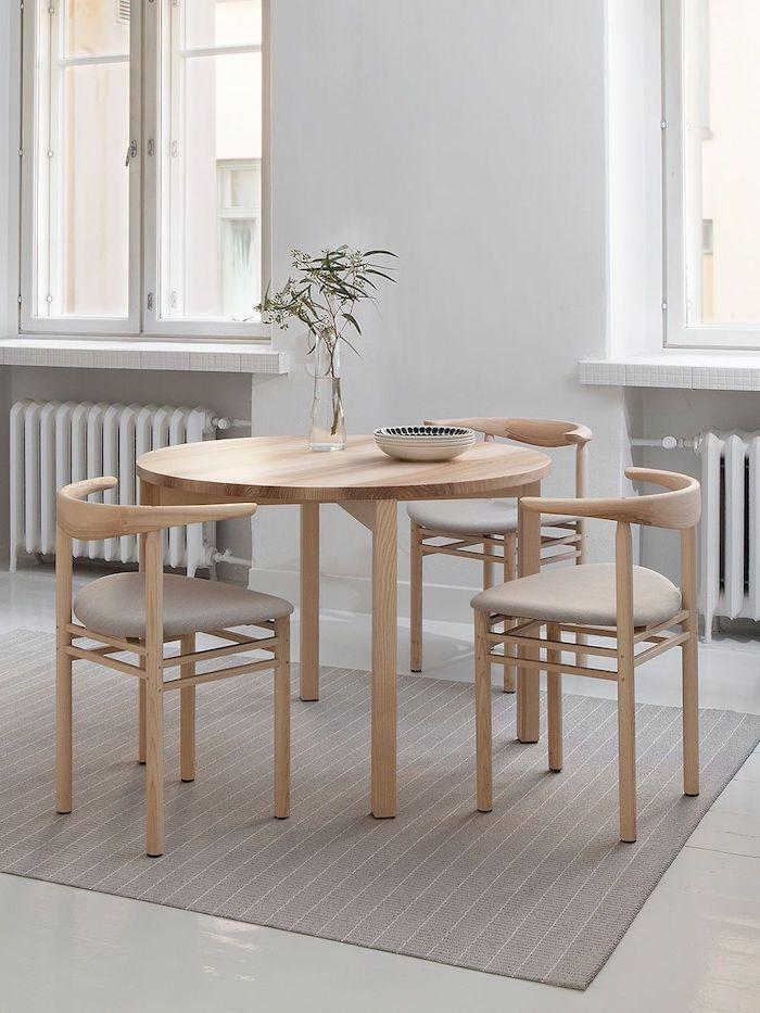 esszimmer einrichten ideen runder vierbeiniger tisch aus holz scandi style möbel interior design minimalistisch drei essstühle beiger teppich schale auf dem tisch