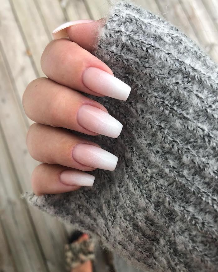 flauschiger grauer pullover frau mit gepflegter maniküre lange fingernägel gelnägel babyboomer weiß rosa farbe nageltrends 2020