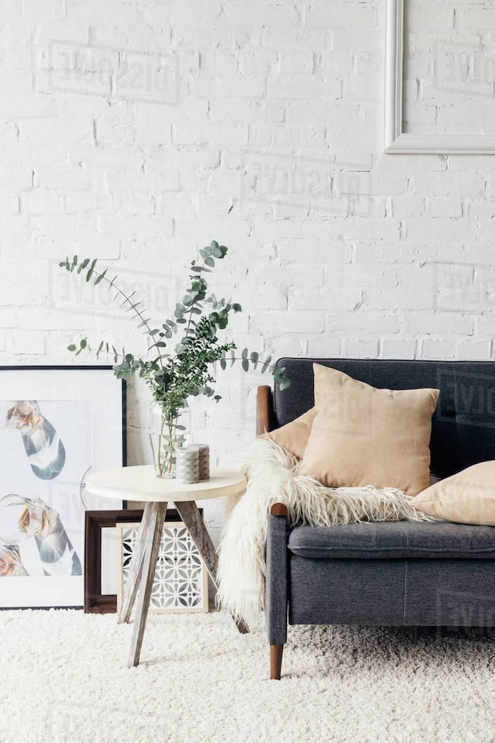 flauschiger teppich weiß couch grau mit beinen aua holz cremefarbene kissen weiße ziegelsteinwand kleiner runder tisch vase mit grüner pflanze modernes bild angelehnt an wand wohnzimmewand ideen
