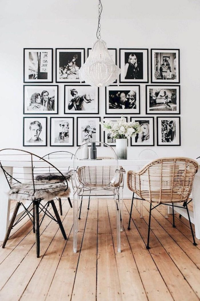 fotowand mit schwarz weißen fotos dekoartikel wohnzimmer essbereich weißer tisch verschiedene stühle hängende lampe vase mit weißen blumen