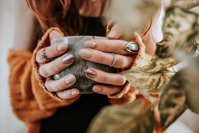 frau mit eine graue tasse nageldesign herbst zwei hände mit beigem nagellack grüne bälätter einer pflanze