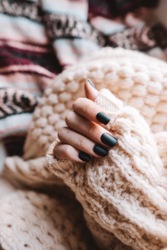 frau mit einem kuscheligen weißen pullover eine hand einer frau mit fingern mit dunkelgrünem nagellack
