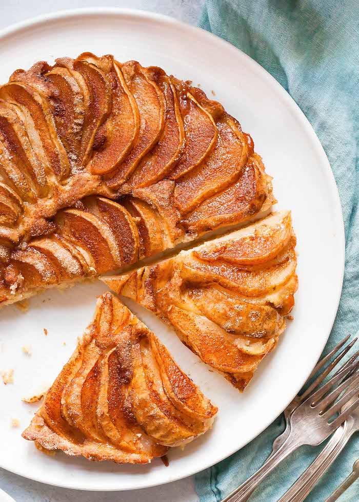 gabel und ein weißer teller mit geschnittenen äpfeln eine blaue deke kuchen rezepte einfach und schnell mit wenig zutaten