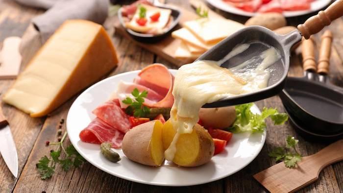 geschmolzener käse ein kleines schwarzes pfännchen mit geschmolzenem käse schinken und salami und kartoffel