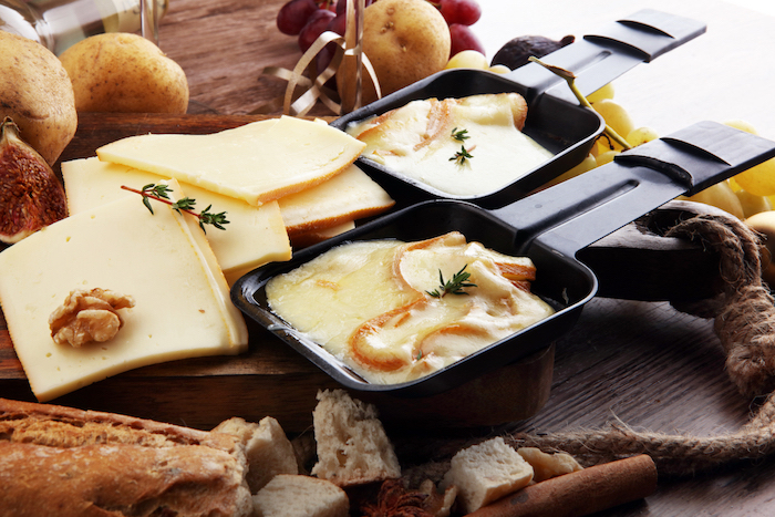 geschnittene champignons und geschmolzenerkäse ein holzbrett und zwei schwarze pfännchen für raclette zutaten