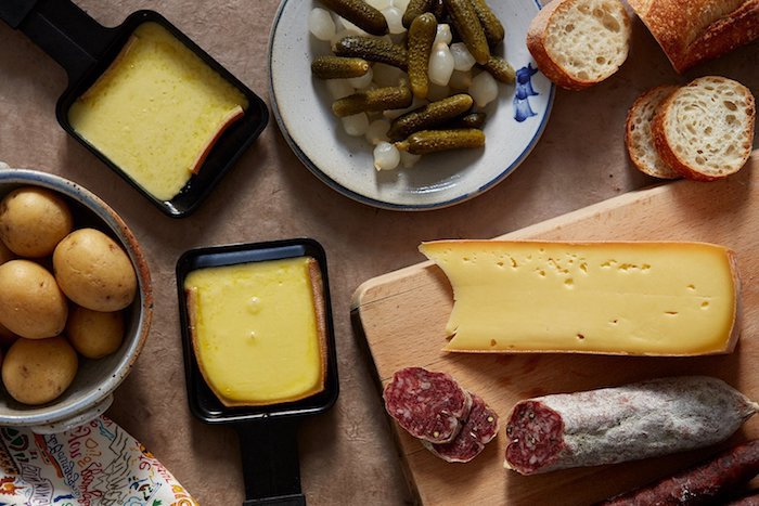 geschnittene salami ein holzbrett raclette zutaten raclette käse ein weißer teller ein schwarzes pfännchen mit käse für raclette