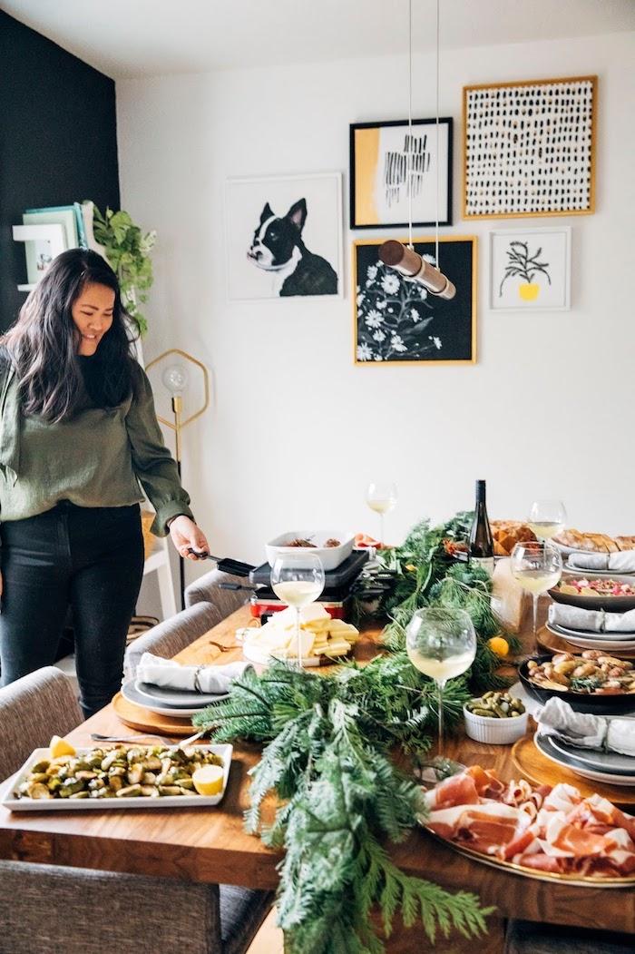 glas mit weißwein ein tisch aus holz raclette zutaten gemüse und gleisch für raclette eine frau bild mit hund