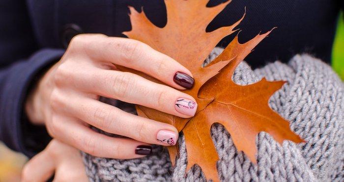 große orange blätter frau mit violettem pullover eine hand mit pinke und violettem nagellack nageldesign herbst