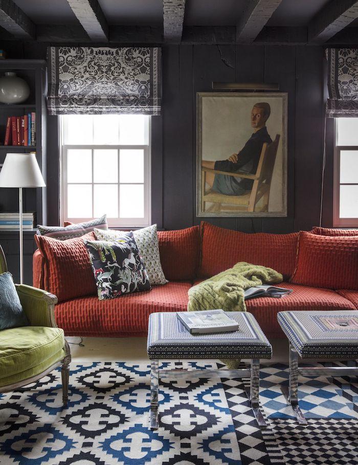 großes couch rot weiß blau schwarzer teppich wohzimmer ideen modern bunte kissen großes gremälde von einem mann schwarze jalousien