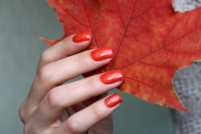großes rotes blatt eine hand mit roten fingernägeln eine frau mit rotem nagellack