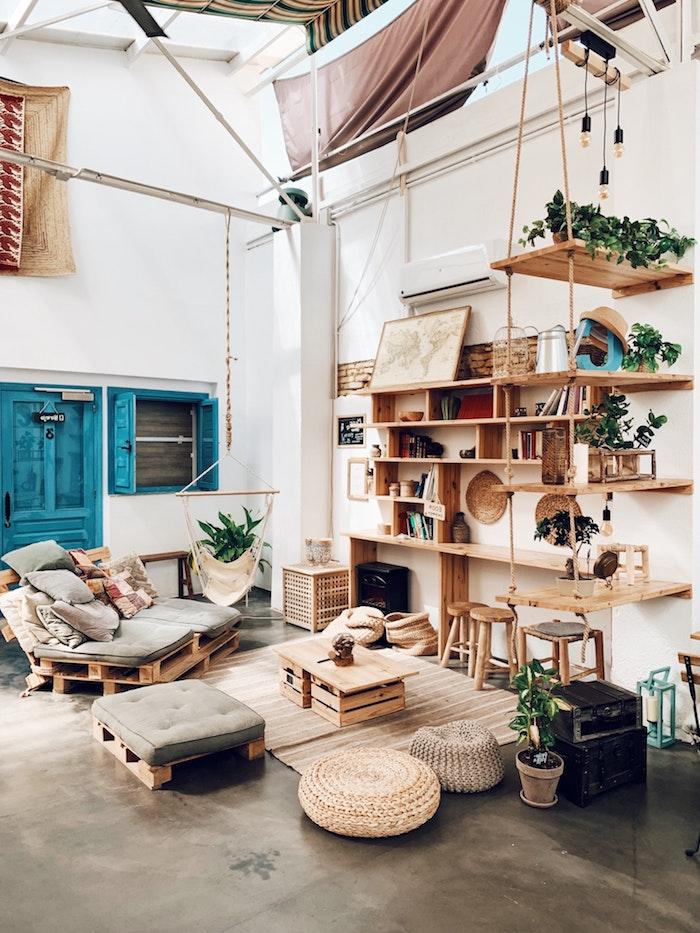 großes wohnzimmer einrichten beispiele kleiner couch aus kisten blaue tür und fenster boho chic inneneinrichtung holzmotive interior design inspiration