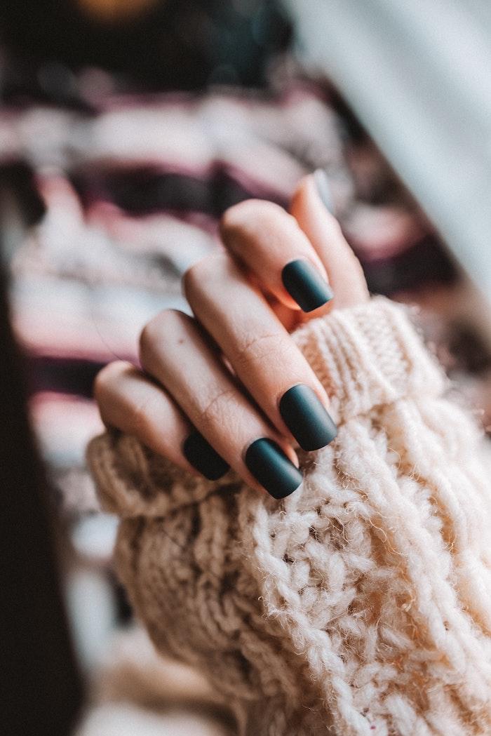 hand einer frau mit einem dunkelgrünen nagellack nageldesign herbst farben für nagellack