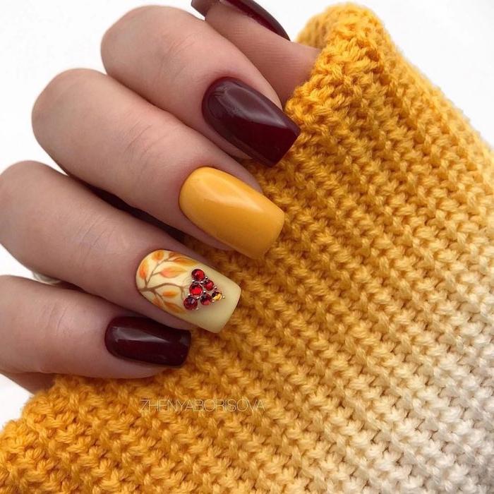 hand mit einem gelben pullover eine hand mit grünem und weinrotem nagellack ideen für nageldesign herbst