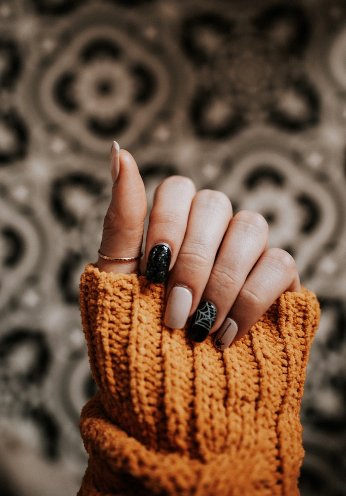 hand mit einem goldenen ring hand mit schwarzem und pinken nagellack rends für den herbs