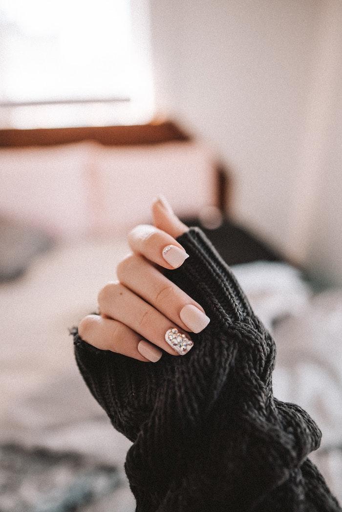 hand mit einem schwarzen pullover und einem beigen und ounken nagellack fenster im schlafzimmer