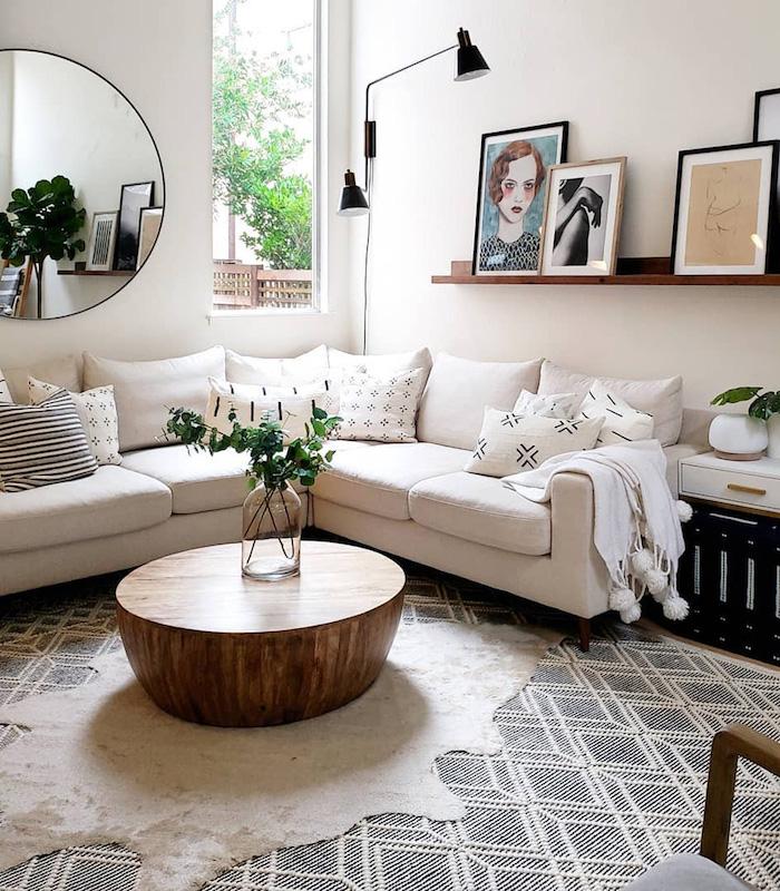 herzstück runder couchtisch aus holz ecksofa weiß dekorative kissen gemälde von frau schwarz weißes foto wanddekoration wohnzimmer schwarz weißer teppich runder spiegel stilvolle deko für das wohnzimmer