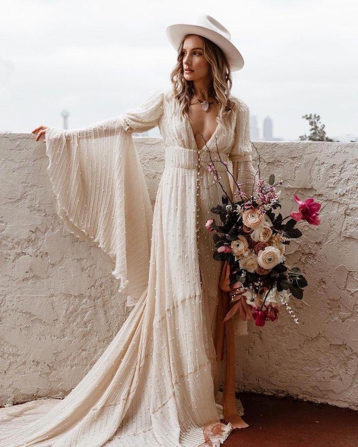 hippie böhmisches hochzeitskleid maxi mit langen ärmeln tiefer v ausschnitt blumenstrauß aus weißen rosen weißer hut accessoire gewellte haare