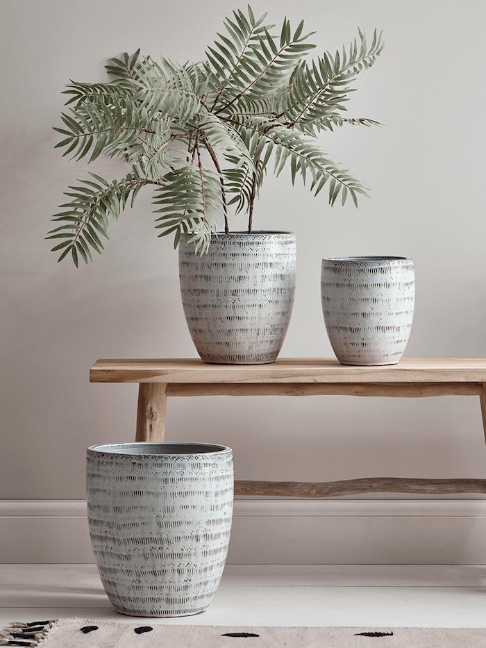 holzbank große graue zimmerpflanzetöpfe grüne pflanze skandinavische deko wohnzimmer blassrosa wandfarbe beiger teppich mit schwarzen kreisen