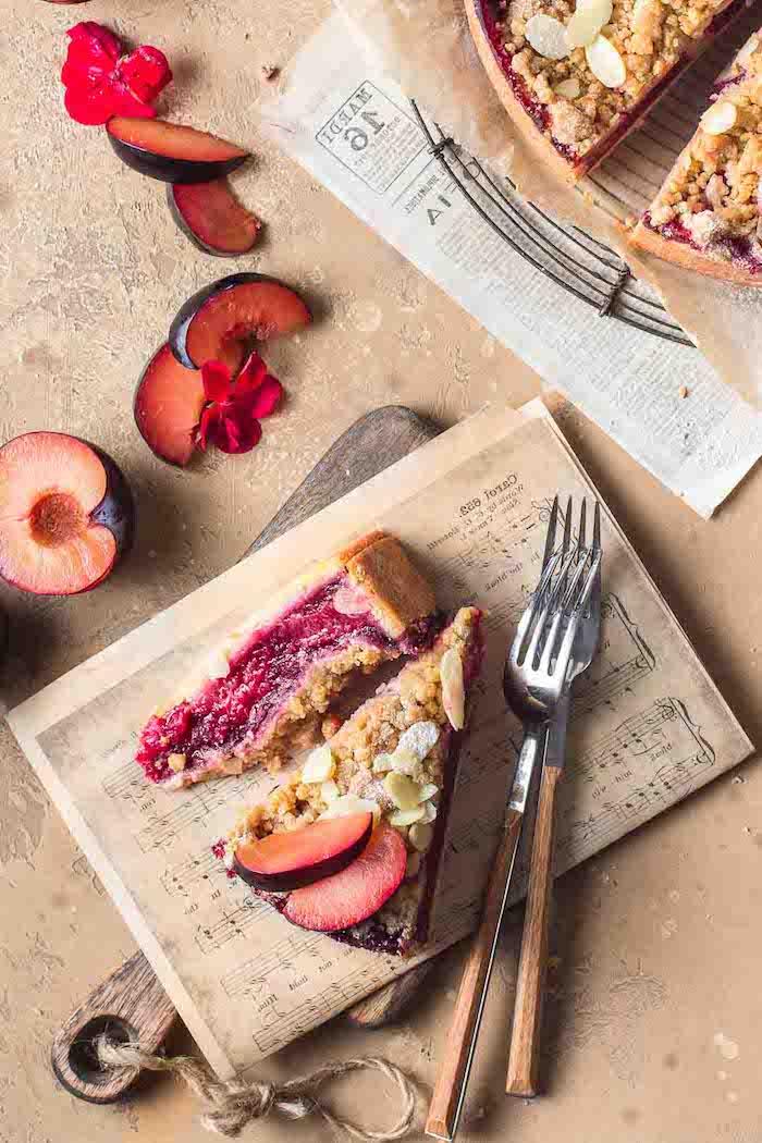 holzbrett und gaabel ein kuchen mit frischen pflaumen kleine rote blumen zur dekoration