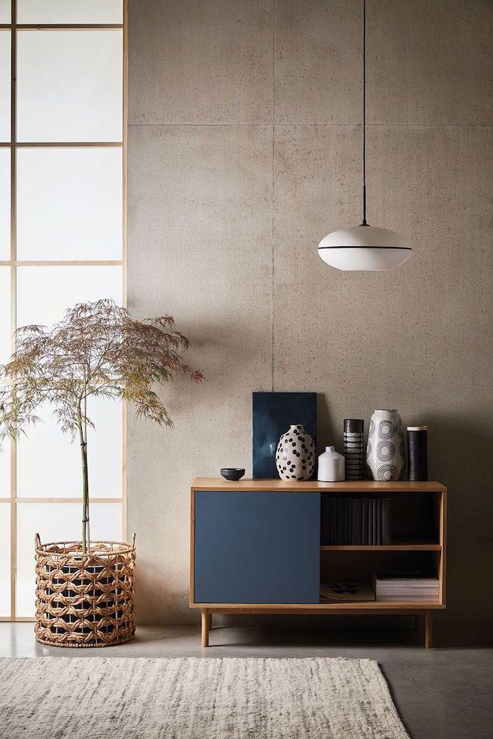 holzkomode dunkelblaue türe japandi inneneinrichtung skandinavische deko wohnzimmer korb topf dekoratover baum vasen verschiedene muster