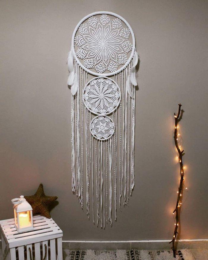 holzzweig dekoriert mit leuchten graue wand weißer großer traumfänger inspo wandhänger mit federn weißer kasten laterne mit leuchtende kerze