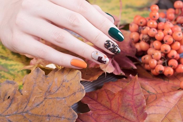 ideen für nageldesign herbst eine hand mit orangem und dunkelgrünem nagellack große orange und rote blätter
