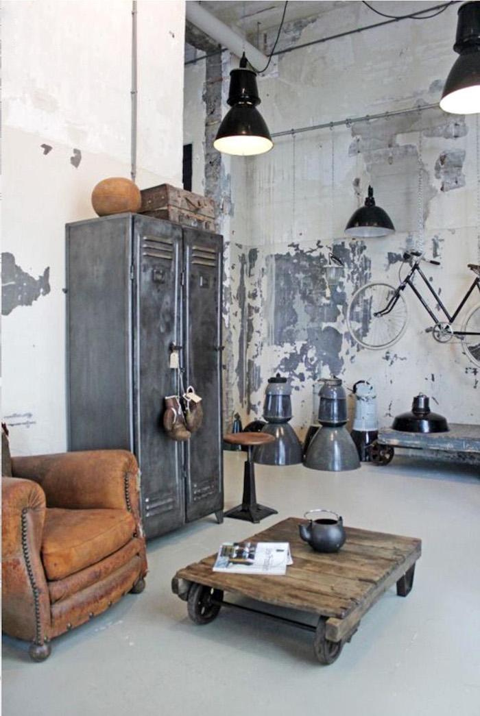 industrial chic style wohnzimmer einrichtungsideen ledersessel braun niedriger holztisch mit rädern kleiderschrank aus metall braune boxhandschuhe aufgehängtes fahrrad an die wand