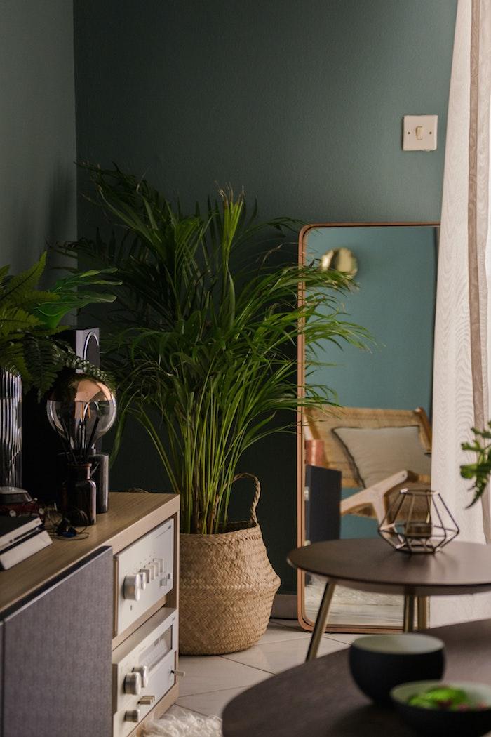 interior design 2020 ideen und inspiration wohnzimmer einrichten große grüne pflanzen minimalistischer spiegel wandfarbe grün runder tisch schwarz stilvolle deko