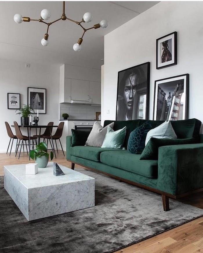 interior design inspiration 2020 große schwarz weiße fotos an die wand stilvoller grüner couch weißer kaffeetisch aus marmor wohnzimmer einrichten modern grauer teppich