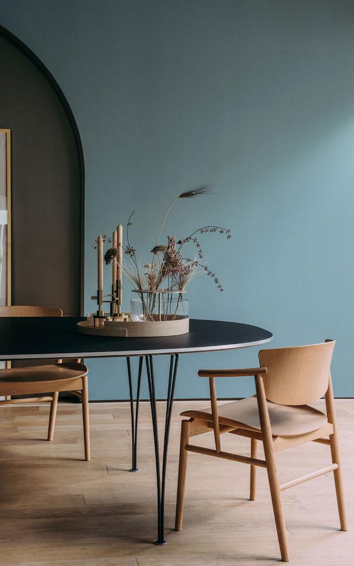 interior design inspiration scandi style möbel minimalistisch großer schwarzer tisch stühle aus holz japandi inneneinrichtung wandfarbe blau grün