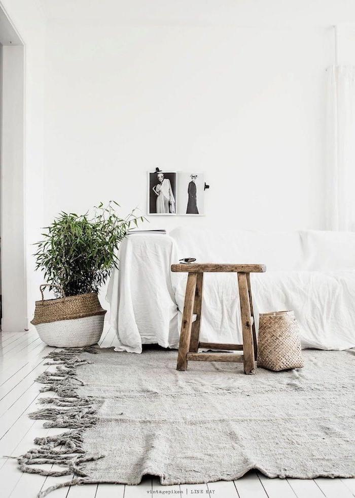 interior design scandi style wohnzimmer korb topf dekoratiover kleiner baum hocker skandinavisch aus holz großer couch bedeckt mit weißer decke schwarz weiße bild an die wand