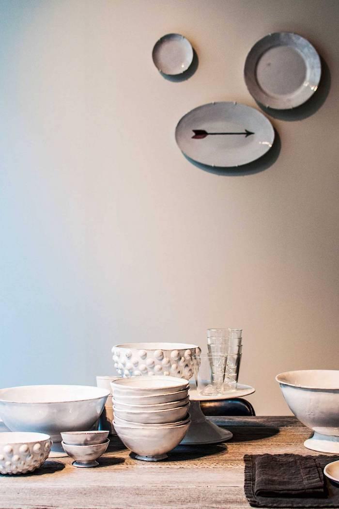 keramische teller schalen kleine tassen großer esstisch aus holz geschirr set skandinavisches design minimalistisches design