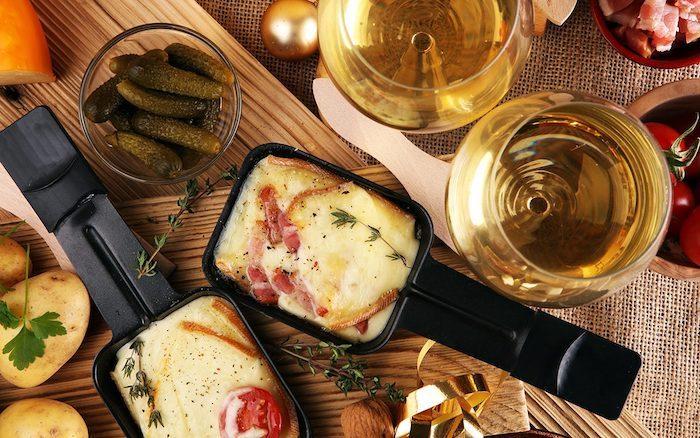 kleine gurken und zwei gläser mit weißwein ein holzbrett zwei schwarze pfännchen mit tomaten und schinken und käse