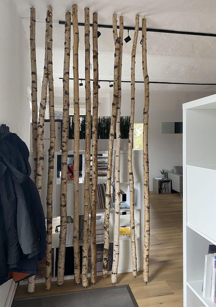 kleine wohnung einrichten wohnzimmer ausstattung birkenstamm raumteiler bodebelag holz weiße wände kleiner bücherregal dekoration grüne pflanzen