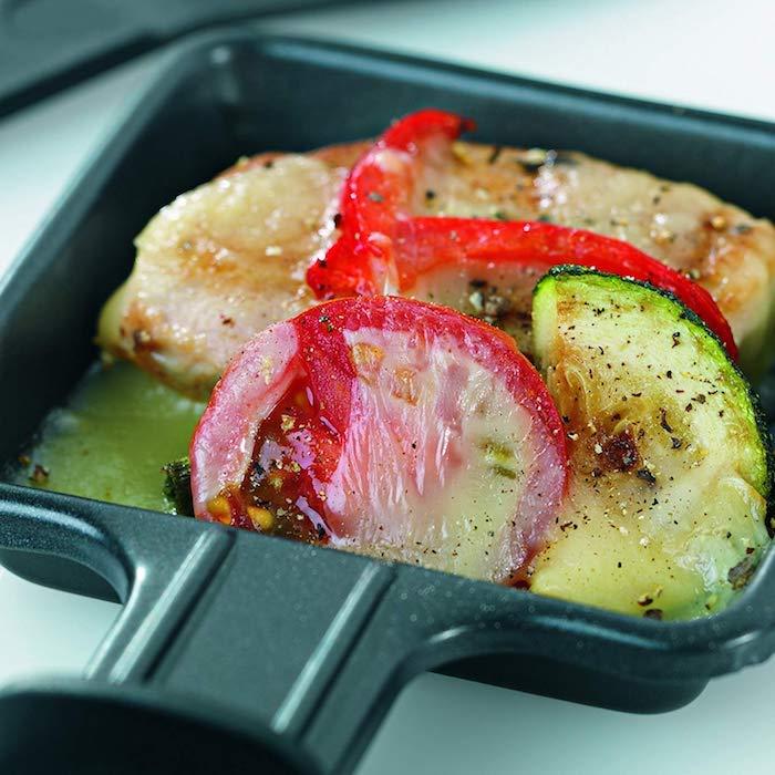 kleines schwarzes pfännchen mit geüse rote paprikaschotten raclette käse und gewürze raclette zutaten ideen