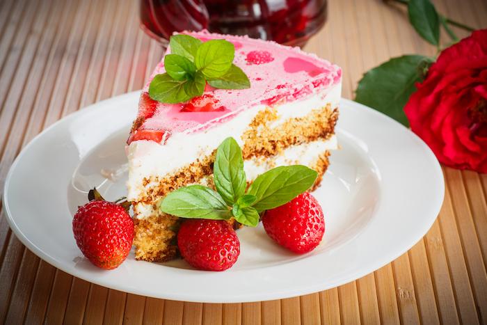 kuchen schnell und einfach weißer teller mit einem kuchen mit guark und roten erdbeeren eine groé rote rose kuchen rezepte einfach und schnell mit wenig zutaten