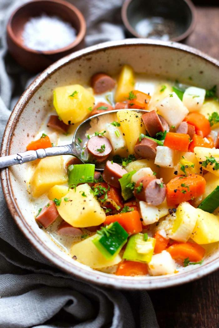 löffel und eine schüssel mit einer suppe mit kartoffeln wiener würstchen und möhren salz