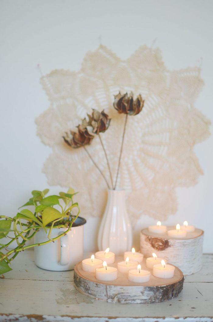 makramee wanddeko blumenmuster weiße vase blumen holzstamm deko holzscheiben kerzenhalter teelichter dekoration wohnzimmer inspo