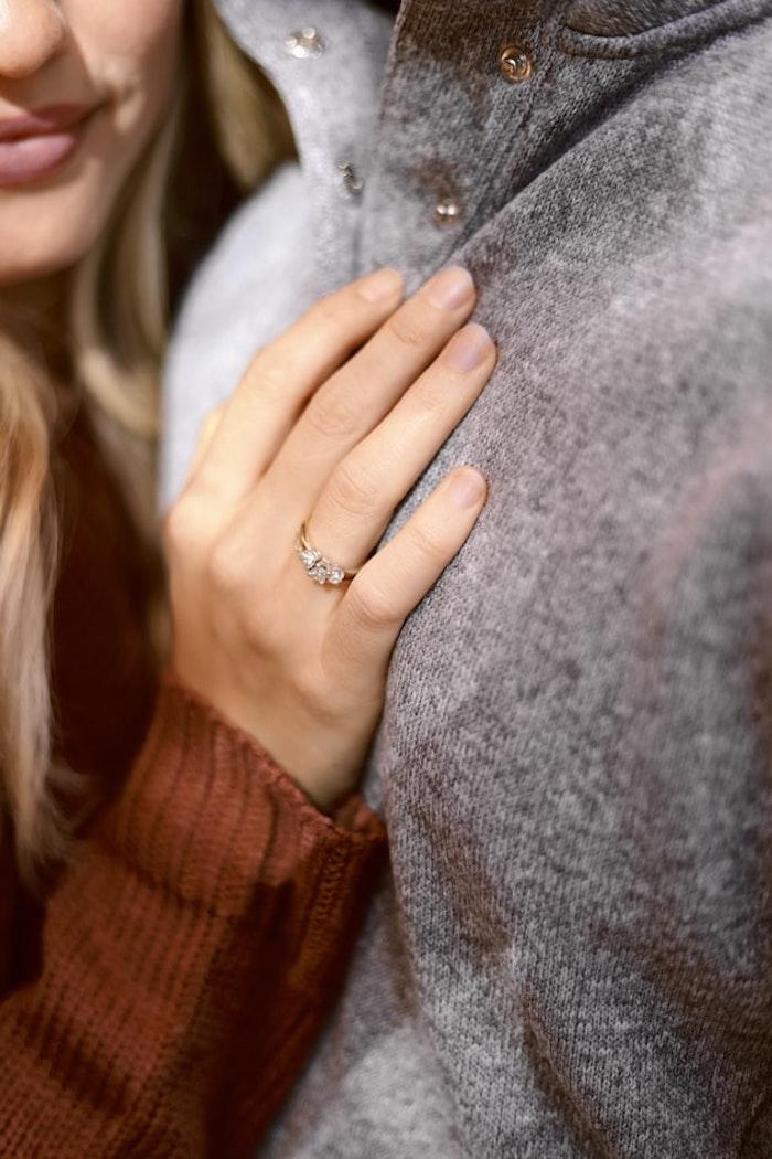 mann mit grauem ullover und eine frau mit ring und einem beigen nagellack nageldesign herbst ideen