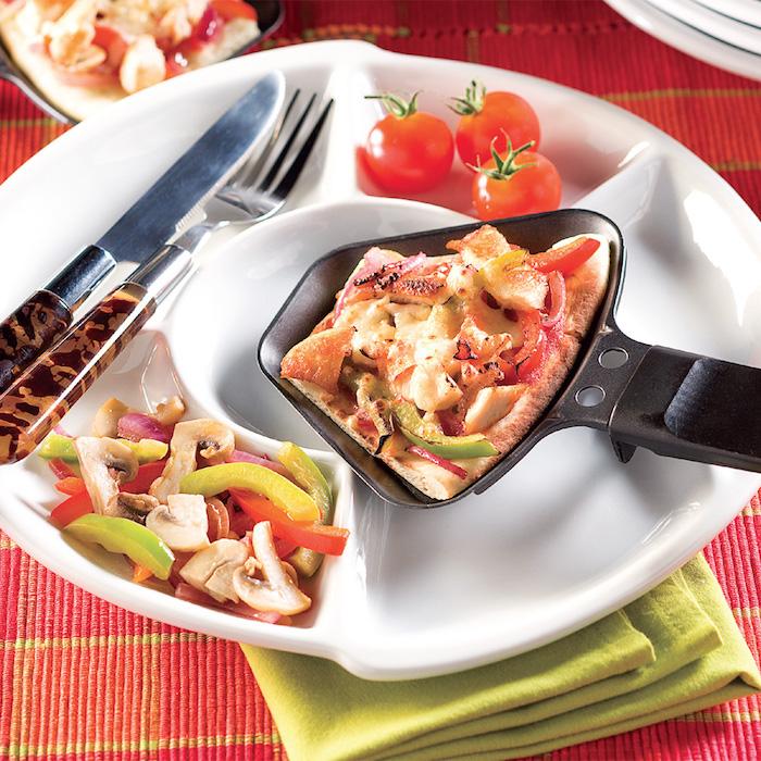 messer und gabel weißer teller mit champignons und kleinen roten tomaten raclette zutaten ideen ein pfännchen