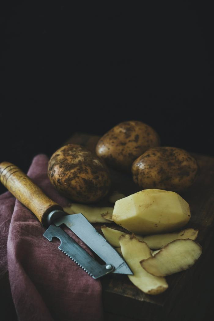 messer und geschnittene große hellgelbe kartoffeln für cremige suppe