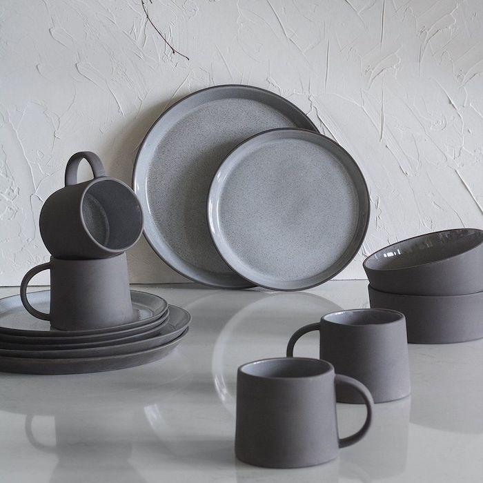minimalistische ästhetik skandinavisches geschirr graue keramische teller tassen schalen besteckset scandi style weiße raue wand marmor tisch